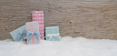 4 small Christmas presents stand in pastel colored fine wrapping paper in the snow. Wooden background