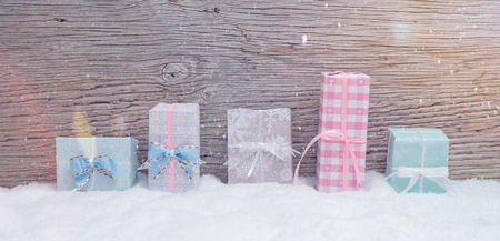 5 small Christmas presents stand in pastel colored fine wrapping paper in the snow. Wooden background with snowfall and lens flares. Zdjęcie Seryjne