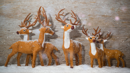 Figures that look like deers are standing in the snow. Its snowing. Wooden background. Zdjęcie Seryjne