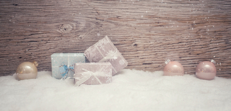 3 small Christmas presents stand in pastel colored fine wrapping paper in the snow. Wooden background with snowfall