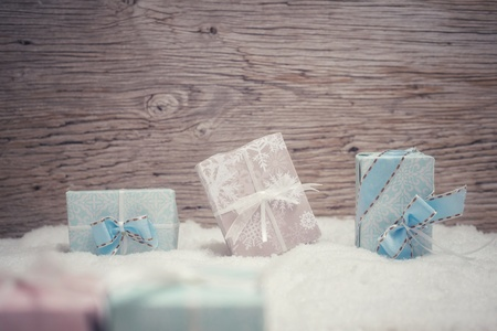 5 small Christmas presents stand in pastel colored fine wrapping paper in the snow. Wooden background Zdjęcie Seryjne
