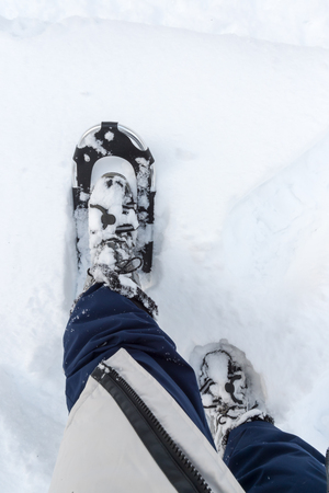 A woman in winter clothes wears snowshoes and stomps in high snow. Personal perspective.