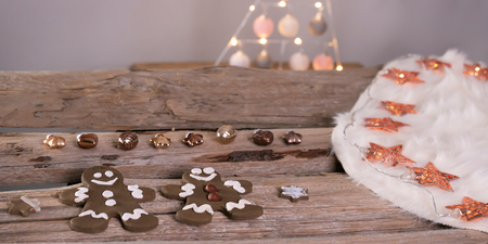 Gingerbread men lie with bronze colored Christmas tree pendants on a white lambskin. The coat is on old wooden beams. Rosé golden fairy lights with stars.