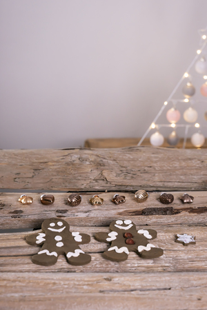Gingerbread men lie with bronze colored Christmas tree pendants on old wooden beams. Zdjęcie Seryjne