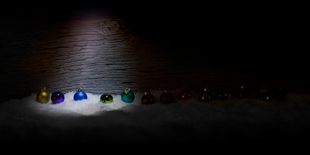 Darkness at Christmas time. Colorful christmas balls lie in the snow. A light comes from above and makes the balls shine and the snow sparkle.