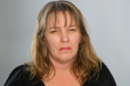 Portrait of a fair skinned woman 40 years from Germany. She makes disgusted face.