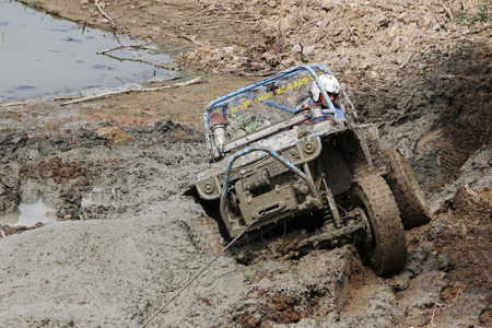 scaling: Off-road vehicle scaling uphill through mud with car winch