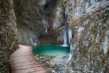 Wood bridge to frozen Waterfall with icicles and green water Stock Photo