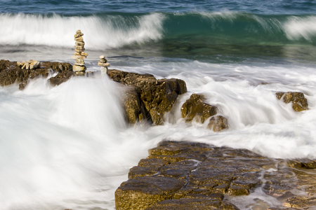 man made object: Stone totems with big sea waves