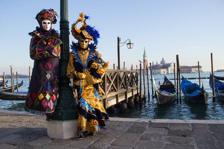 Couple of Venetian Masks on Venice Carnival with Gondolas