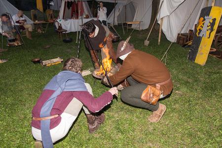 vestidos de epoca: Medieval People make Fire in Camp Editorial