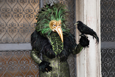 Venetian Mask of Male with Bird in green / black elegant costume on on San Zaccaria Square in Venice. Editorial