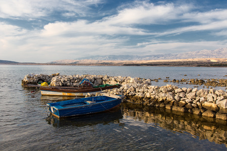 Wooden rowboat - Old fishing boats in old stone sea harbour on island Pag, Croatia