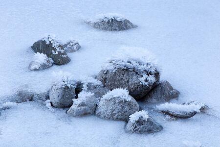 Frozen rocks on River in winter 写真素材