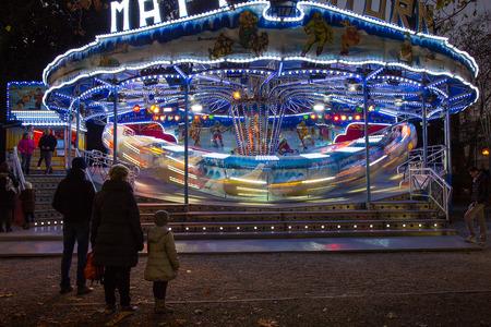 Carousel in the night - Family in Amusement park - Fair Fiera di SantAndrea, Gorizia, Italy Editorial