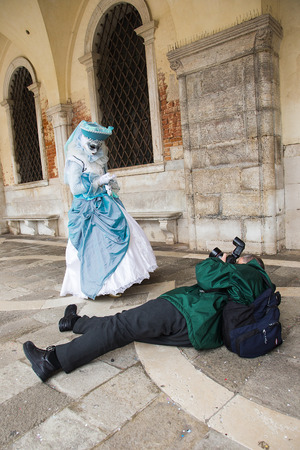 Venice Carnival - Photographer taking pictures of Venetian mask on St. Mark's Square in Venice.