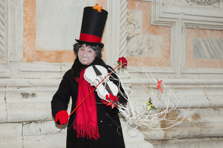 Venetian Mask of Male Pierrot playing white violin with red rose on San Zaccaria Square - Venice Carnival