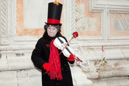 Male Pierrot playing violin with red rose on San Zaccaria Square, Venice, Italy - Venice Carnival Editorial