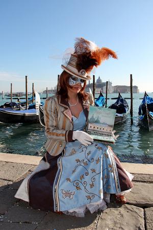 Female Venetian Mask in blue elegant carnival costume with traditional venetian gondolas - Venice Carnival