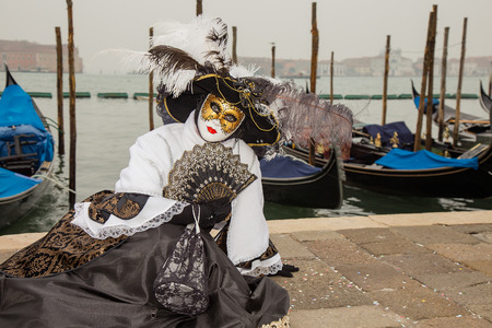 Portrait of Female Venetian Mask in black and white elegant costume with venetian gondolas, St. Marks Square, Venice, Italy