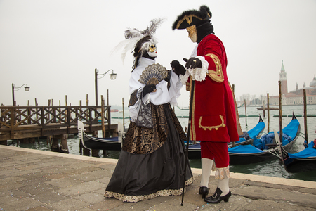 Venice Carnival - Couple in love of Venetian masks on St. Marks Square in Venice with Gondolas in background.