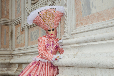 Female Venetian Mask in light pink elegant carnival costume,Venice Carnival, Italy.