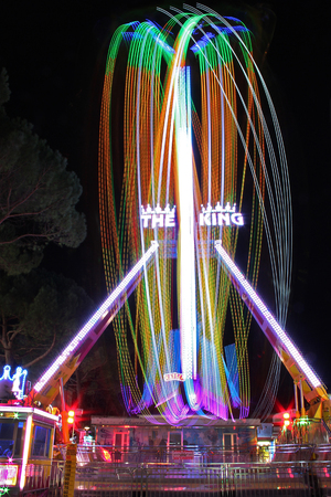 Spinning ferris wheel in the night with coloured lights trails. Editorial