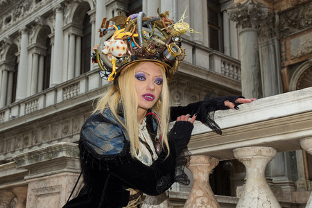 Venice Carnival - Vampire Portrait - Female Venetian Mask with magic blue eyes, vampire teeth, long blonde hair and unique artistic hat on St. Marks Square in Venice.