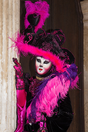 Cat mask - Female Venetian Mask in pink  black elegant costume on St. Marks Square in Venice with traditional venetian pillar - Venice Carnival