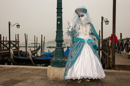Female Venetian Mask in blue elegant carnival costume with traditional venetian gondolas - Venice Carnival