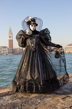 Venice mask - Female Venetian Mask in black dress with Venice in background, island San Giorgio, Venice, Italy