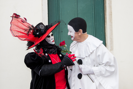 Couple of Venetian Masks - Pierrot and woman in red with Rose on San Zaccaria Square in Venice, Italy