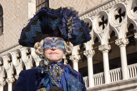 Venetian Mask of Male Gantleman with eye mask and venetian pillar in background, Venice Carnival, Italy