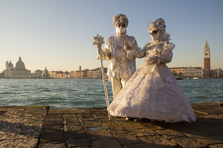 Couple of Venetian Masks in white drasses, Venice Carnival with Venice in background, island San Giorgio, Venice, Italy