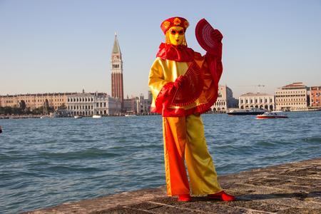 Female Venetian Mask with Venice in background, island San Giorgio, Venice, Italy 報道画像