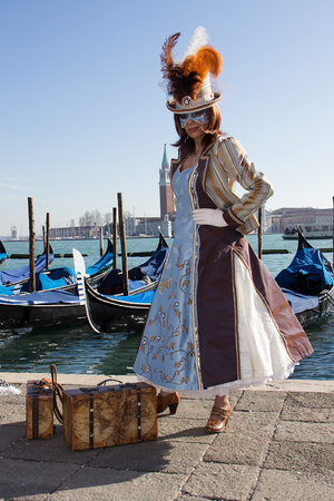 Venetian Mask - Beautiful Woman with Gondolas on Venice Carnival Editorial