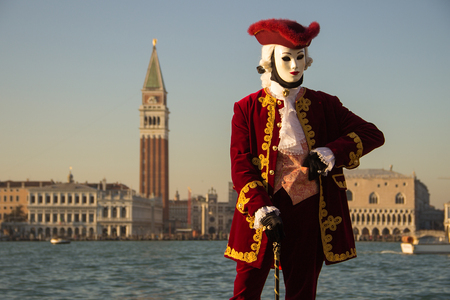 Venetian Mask of Male Gantleman in red dress with Venice in background, island San Giorgio, Venice, Italy