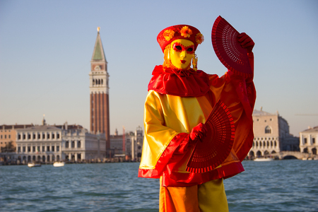 Female Venetian Mask with Venice in background, island San Giorgio, Venice, Italy Editorial