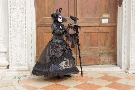 Venetian Mask of Woman with Bird in green  black elegant costume on on San Zaccaria Square in Venice.