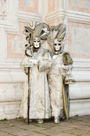 Venice Carnival - Lovely Couple of Venetian masks in white and gold elegant costume on San Zaccaria Square in Venice. Editorial