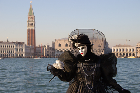 Venice Carnival - Female Venetian Mask in black dress with Venice in background, island San Giorgio, Venice, Italy