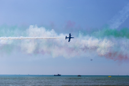 Fly of solo pilot of Frecce Tricolori Italian acrobatic aircraft team, Grado beach, Italy Editorial