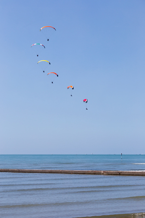 Airshow exibition of multicolored powered parachutes, Grado beach, Italy.