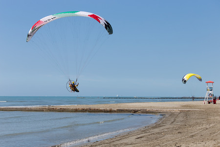 Powered parachutes Air show - multicolored Paratroopers landing on Grado beach, Italy Editorial