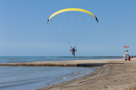 Powered parachutes landing on the Grado beach, Italy