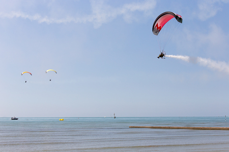 Powered parachutes Air show - multicolored Paratroopers in the sky, Grado beach, Italy Editorial