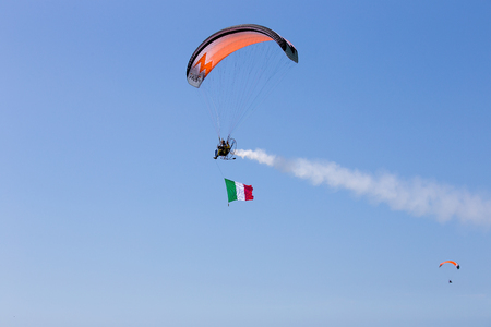 Powered paratrooper during the air with italian flag, Air show Grado, italy