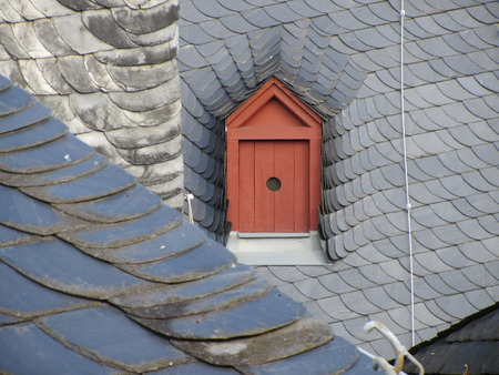 attic window: Attic window on the roof of a house for pigeons.