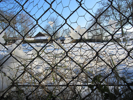 mesh fence: Winter landscape through the wire mesh fence.
