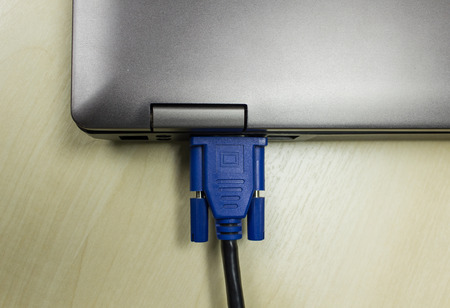 VGA cable connected to laptop on wooden table photo